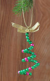 Christmas. Bead work Christmas tree on a branch of spruce Stock Images