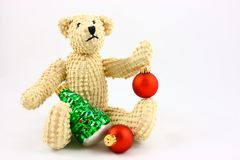Christmas Bear. A small teddy bear sitting on a white background with red and green glass Christmas ornaments. Two red ornaments in traditional ball shape and Royalty Free Stock Images