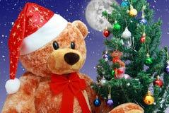 Christmas bear. Bear in Santa hat sit near the Christmas Tree, small cow in the tree Stock Photo
