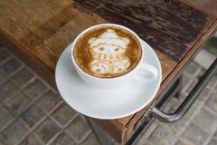 Christmas Bear Coffee Latte Art. Christmas Bear as Coffee Latte Art drink for Christmas Festive on arm of garden bench Stock Photography