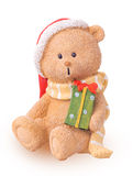 Christmas bear in a Santa Claus hat holding a gift in their hand Stock Photography