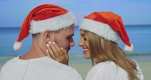 Christmas beautiful beach couple. Wearing Santa hat in summer sun in love on travel holidays on tropical travel destination during winter holidays stock video footage