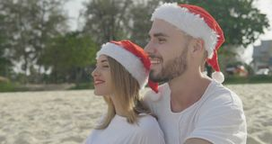 Christmas beautiful beach couple. Wearing Santa hat in summer sun in love on travel holidays on tropical travel destination during winter holidays stock footage