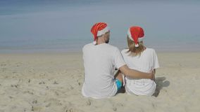 Christmas beautiful beach couple. Wearing Santa hat in summer sun in love on travel holidays on tropical travel destination during winter holidays stock video