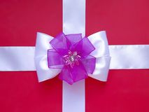 Christmas beautiful bowknot on the wrapping red box. Red gift box is wrapping white silk ribbon with attractive bowknot. Purple flower on red and white royalty free stock photos