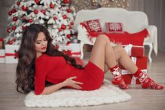 Christmas. Beautiful brunette santa girl. Smiling woman in red d. Ress with long hair and red lips makeup lying on white knitted chunky yarn blanket by xmas snow Stock Image