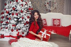 Christmas. Beautiful brunette santa girl. Smiling woman in red d. Ress with long hair and red lips makeup present gift box on white knitted chunky yarn blanket royalty free stock image