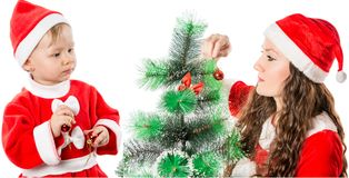 Christmas. Beautiful mom and child girl in santa costume decorating christmas tree. Royalty Free Stock Photo