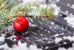 Christmas beautiful red ball with fir branch and snow on computer keyboard Royalty Free Stock Image