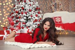 Christmas. Beautiful santa girl. Smiling woman with long hair an. D red lips makeup lying on white knitted chunky yarn blanket in home by xmas snow over boke Royalty Free Stock Images