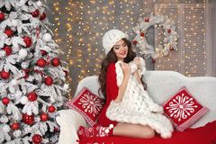 Christmas. Beautiful santa girl. Smiling woman with long hair si. Tting on cozy sofa holding white knitted chunky yarn blanket in home over xmas snowflakes tree Royalty Free Stock Photos