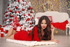 Free Christmas. Beautiful Santa Girl. Smiling Woman With Long Hair And Red Lips Makeup Lying On White Knitted Chunky Yarn Blanket In Royalty Free Stock Image - 135366546