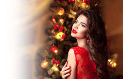 Christmas. Beautiful smiling brunette woman portrait. Red lips m. Akeup. Fashion earring jewelry. Curly hair style. Elegant lady in red dress over christmas tree Stock Photography