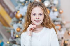 Christmas. Beautiful smiling girl. Over christmas tree lights background. happy new year. Royalty Free Stock Image