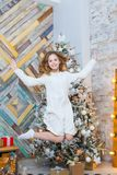 Christmas. Beautiful smiling girl. Over christmas tree lights background. happy new year. jumps Royalty Free Stock Photo