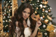 Christmas. Beautiful smiling woman with carnival mask. Fashion e Stock Photography