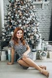 Christmas. Beautiful smiling woman Red long hair. Elegant over christmas tree lights background. happy new year. Christmas. Beautiful smiling woman. Manicure royalty free stock photos