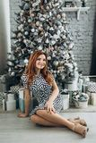 Christmas. Beautiful smiling woman Red long hair. Elegant over christmas tree lights background. happy new year. Christmas. Beautiful smiling woman. Manicure stock images