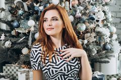 Christmas. Beautiful smiling woman Red long hair. Elegant over christmas tree lights background. happy new year. Christmas. Beautiful smiling woman. Manicure stock photos