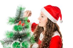 Christmas. Beautiful woman in santa costume decorating christmas tree. Stock Photos