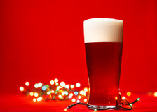Christmas beer. Full glass of bear or ale with christmas lights on red background Stock Image