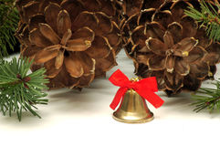 Christmas bell and cones. A christmas bell in pine cones background Royalty Free Stock Photo