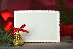 Christmas bell and empty vintage Christmas photo frame. On wooden background Royalty Free Stock Images