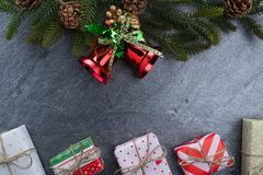 Christmas bell fir gift box with text happy christmas on stone. Background Royalty Free Stock Image