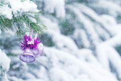 Christmas bell frosty is lying on a pine tree in the snow. Stock Photo
