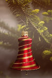 Christmas bell. Red Christmas bell with gold stripes on the branch Royalty Free Stock Image