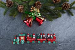 Christmas bell and toy train on stone. Background Royalty Free Stock Photo