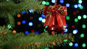 Christmas bell for tree decoration on holiday background colorful blurred garlands stock footage