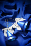 Christmas bells. Two Christmas bells over dark blue fabric background Stock Photography