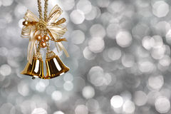 Christmas bells. Gold Christmas bells on silver blurred background Stock Images