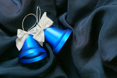 Christmas bells. Two Christmas bells over dark blue fabric background Royalty Free Stock Photos