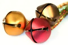 Christmas Bells. Bronze, gold and red christmas bells with braided rope royalty free stock images