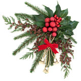 Christmas Bells and Baubles. Christmas flora with gold bells and red bauble decorations with holly, ivy and winter greenery over white background Royalty Free Stock Image