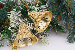 Christmas bells. And fir-tree branch on gray background Stock Images