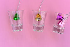 Christmas bells in glass on pink background Royalty Free Stock Images