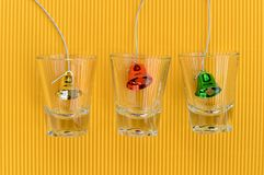 Christmas bells in glass on yellow background Royalty Free Stock Image