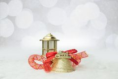 Christmas  bells. Christmas golden bells with red ribbons on the snow Stock Image