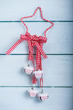 Christmas bells and ribbon hang on wooden background Stock Images