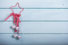 Christmas bells and ribbon hang on wooden background Stock Photography