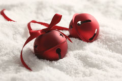 Christmas bells with ribbon in snow stock photography