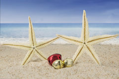 Christmas bells and starfishes on sand Stock Image