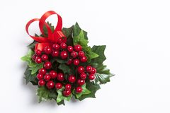 Christmas Berries garland with red ribbon. And green leaves over white background Royalty Free Stock Photo