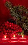 Christmas berries and tea candles. Christmas berries,candles,evergreen branch and pine cones Royalty Free Stock Photography