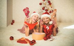 Christmas Best friends girl. girls wearing santa claus clothes. red lingerie for New year. Pretty girl. Wearing lingerie in the Christmas decoration royalty free stock images