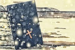 Christmas. Bible and cross on a white background old. Falling snowflakes. Close up royalty free stock photo