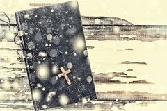 Christmas. Bible and cross on a white background old. Falling snowflakes. Close up stock image